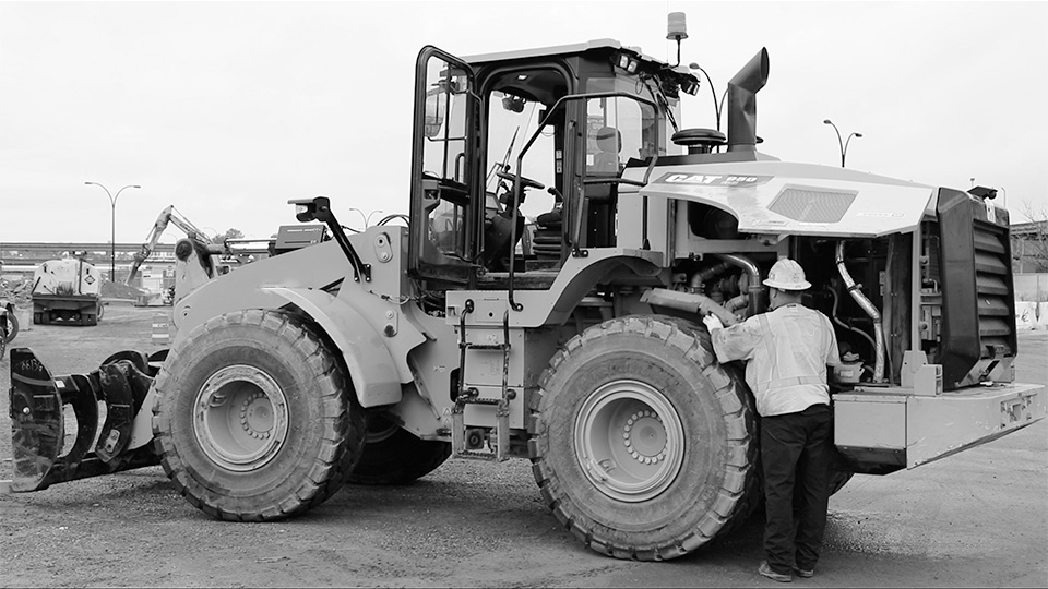 Image of a construction worker doing Equipment Inspections on a wheel loader on a construction site